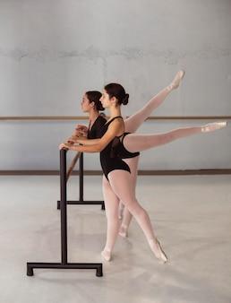 Zijaanzicht van professionele ballerina's die in pointe-schoenen trainen