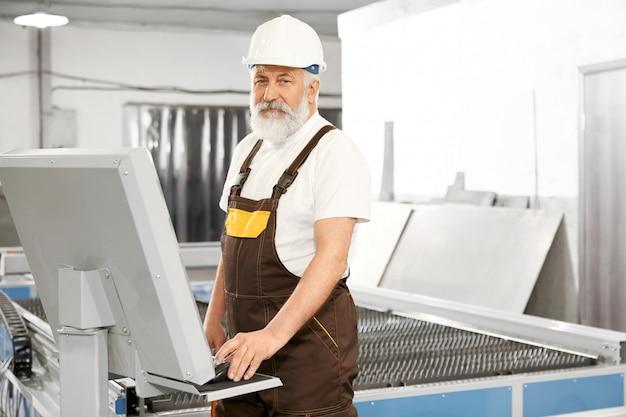 Zijaanzicht van professionele werknemer van metalen fabriek