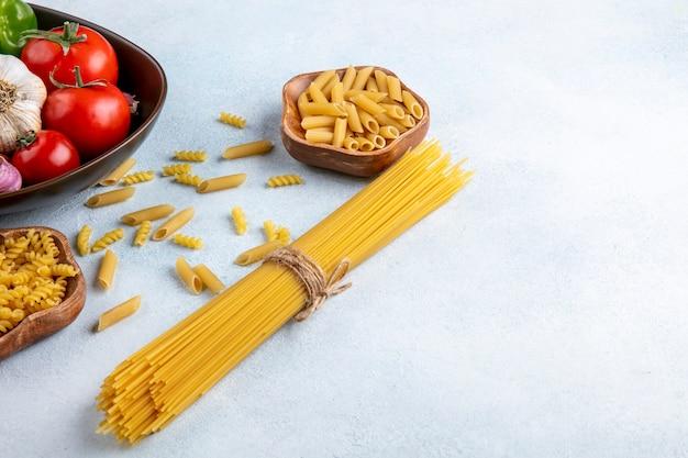 Zijaanzicht van rauwe spaghetti met rauwe pasta in een kom met tomaten en knoflook in een kom op een grijze ondergrond