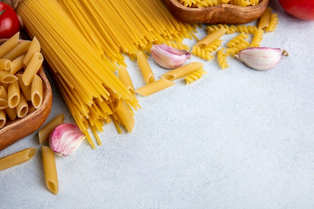 Zijaanzicht van rauwe spaghetti met rauwe pasta in kommen met knoflook op een grijze ondergrond