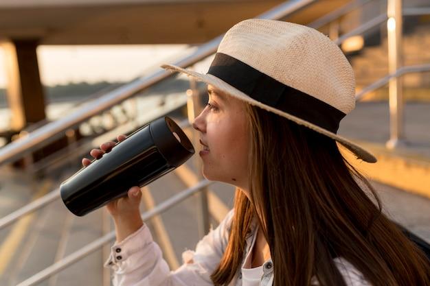 Zijaanzicht van reizende vrouw met hoed die uit thermosfles drinkt
