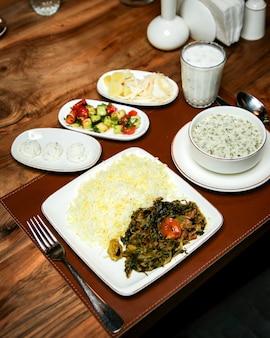 Zijaanzicht van rijst met gestoofd vlees en kruiden op houten tafel