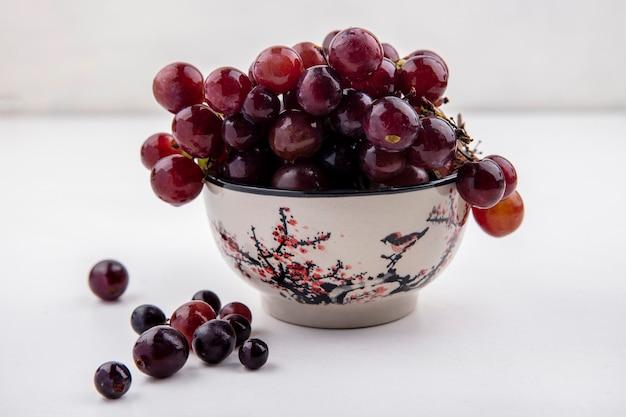 Zijaanzicht van rode druif in kom en op witte achtergrond