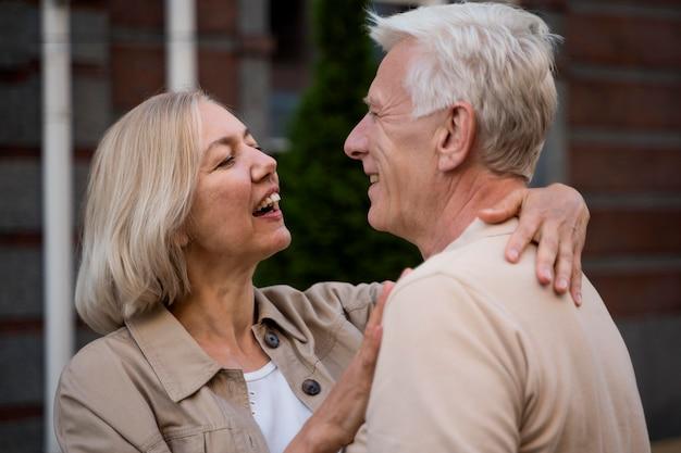 Zijaanzicht van romantisch ouder paar omarmd terwijl we in de stad waren