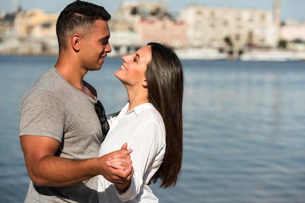Zijaanzicht van romantisch paar knuffelen op het strand