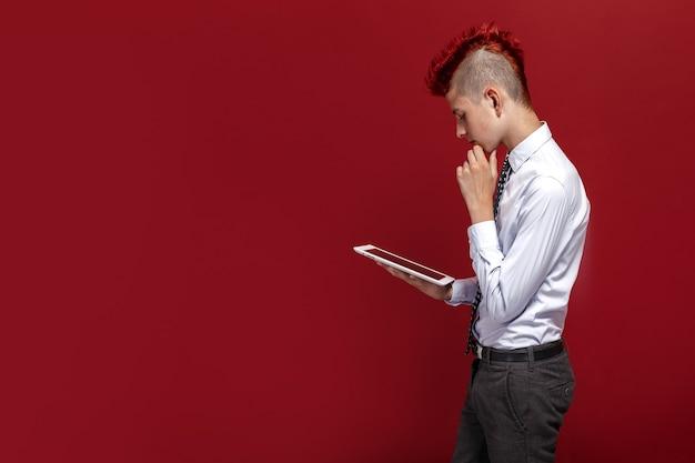 Zijaanzicht van roodharige tienerpunk met tablet tegen van rode geïsoleerde ruimte