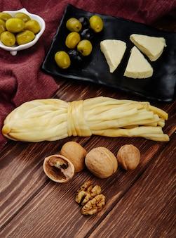 Zijaanzicht van roomkaas in driehoek vorm met ingelegde olijven op een zwarte lade en walnoten met string kaas op donkere houten