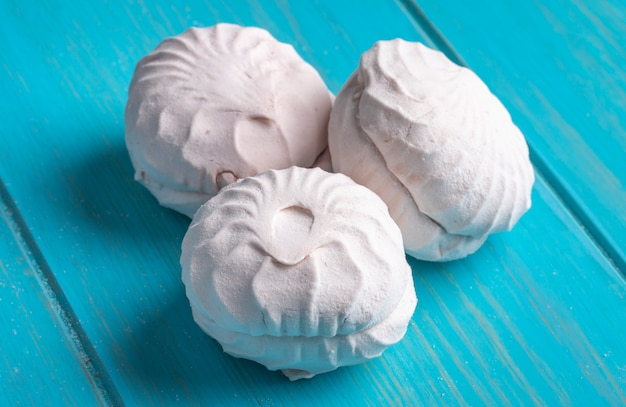 Zijaanzicht van roze zefier of marshmallows op blauw