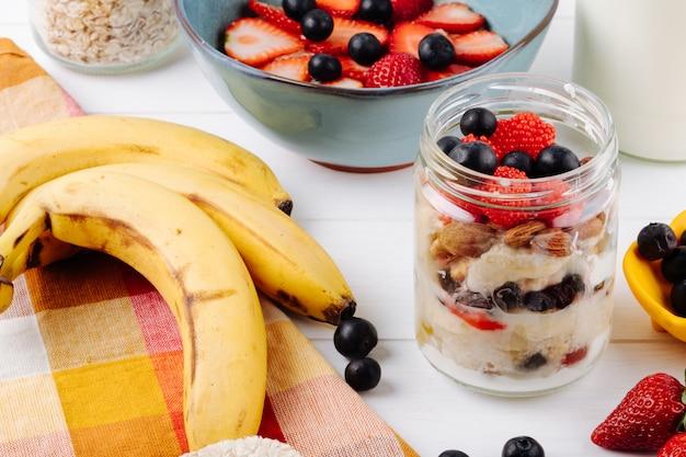 Zijaanzicht van 's nachts haver met verse aardbeien bosbessen en noten in een glazen pot en rijpe bananen op rustieke tafel