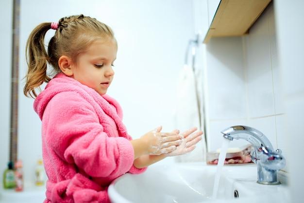 Zijaanzicht van schattig klein meisje met paardenstaart in roze badjas haar handen wassen.