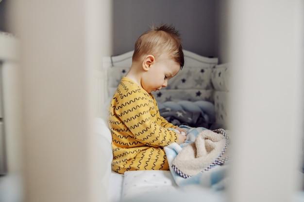 Zijaanzicht van schattige blonde babyjongen die in de ochtend in zijn wieg zit en met zijn favoriete deken speelt.