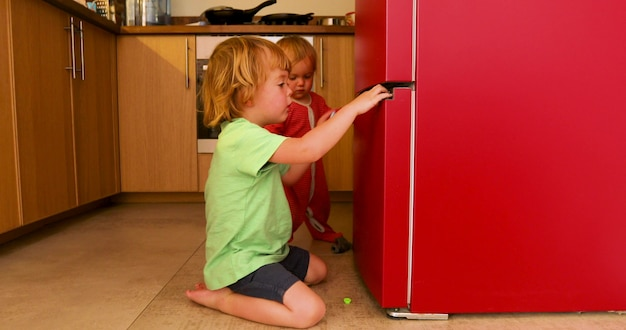 Zijaanzicht van schattige kinderen die en op vloer in keuken dichtbij koelkast zitten spelen