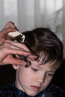 Zijaanzicht van schattige kleine jongen die wordt geknipt door kapper in de kapperszaak.