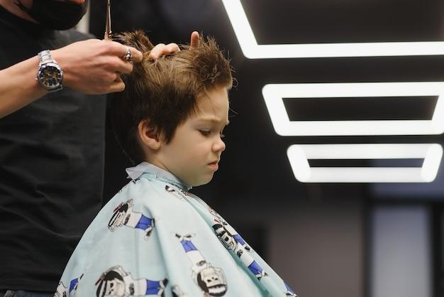 Zijaanzicht van schattige kleine jongen krijgt kapsel door kapper in de kapsalon