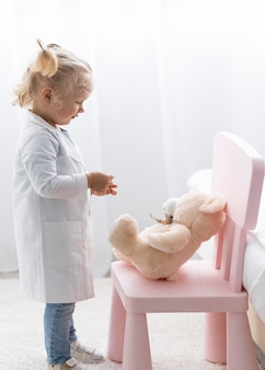 Zijaanzicht van schattige peuter met laboratoriumjas en teddybeer