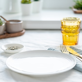 Zijaanzicht van schone lege witte plaat, glas water, vork en mes op wit tafellaken