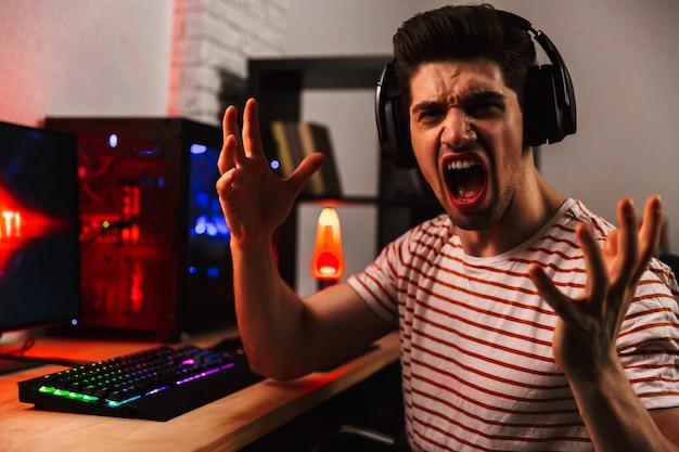 Zijaanzicht van schreeuwende gamer spelen van videospellen op computer