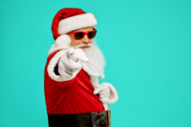 Zijaanzicht van selectieve aandacht op vinger van man in santa claus-kostuum. geïsoleerde portret van senior man met witte baard