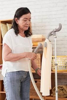 Zijaanzicht van senior huisvrouw stomen blouse