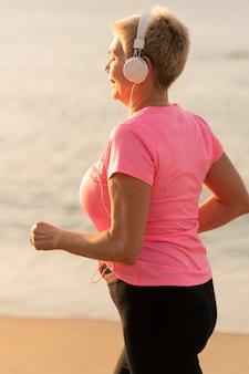 Zijaanzicht van senior vrouw met koptelefoon joggen op het strand