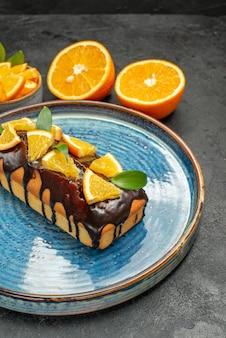 Zijaanzicht van set gele hele en gesneden sinaasappelen smakelijke taarten met mes en vork op donkere tafel