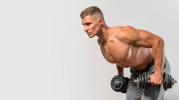Zijaanzicht van shirtless man uit te werken met gewicht