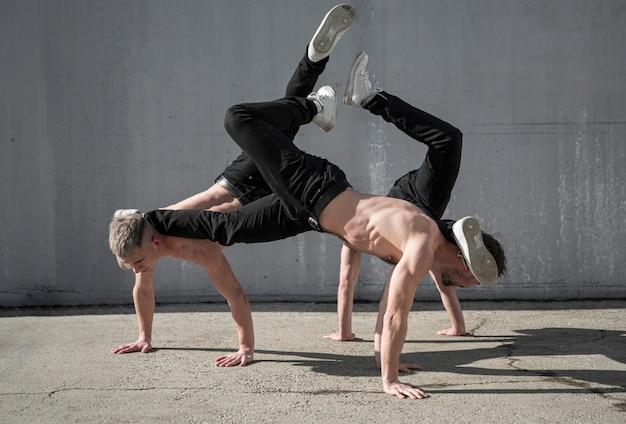 Zijaanzicht van shirtless mannelijke hiphopdansers die samen buiten repeteren