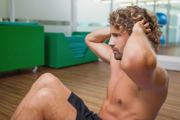 Zijaanzicht van shirtless mens die opdrukoefeningen in gymnastiek doet