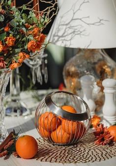 Zijaanzicht van sinaasappelen in metalen mand vaas op tafel