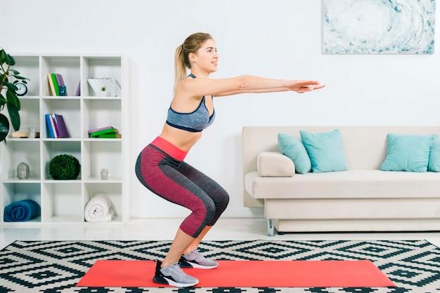 Zijaanzicht van slanke fitness jonge vrouw beoefenen oefening thuis