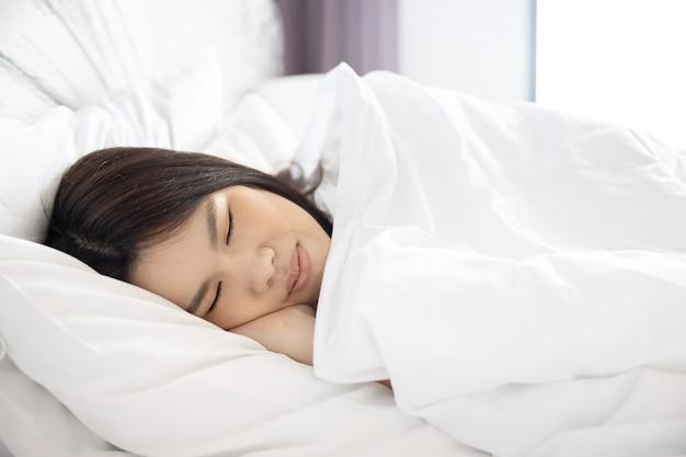 Zijaanzicht van slapende aziatische vrouw op haar bed