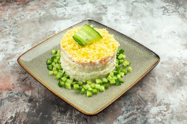 Zijaanzicht van smakelijke salade geserveerd met gehakte komkommer op gemengde kleur achtergrond
