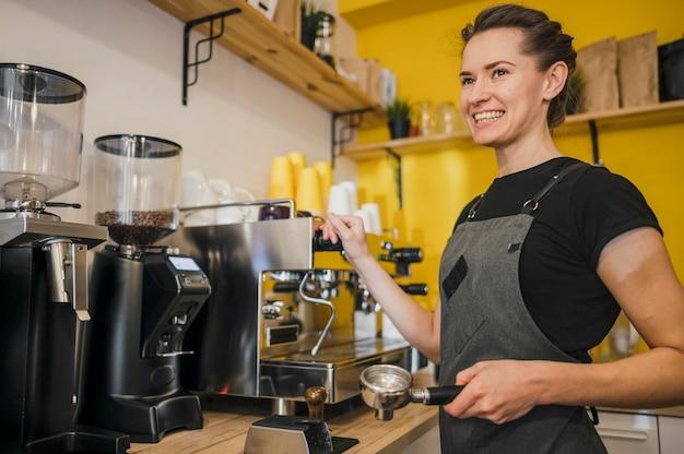 Zijaanzicht van smiley barista met koffiezetapparaat