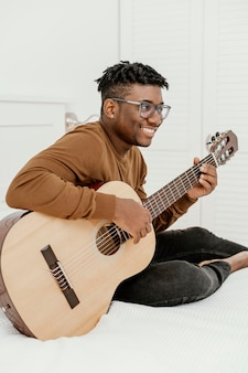Zijaanzicht van smiley mannelijke musicus die thuis gitaar op bed speelt