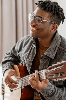 Zijaanzicht van smiley mannelijke musicus thuis gitaarspelen