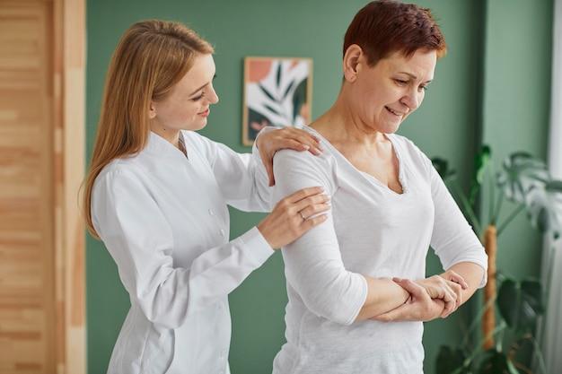 Zijaanzicht van smiley oudere vrouw in covid herstel fysieke oefeningen doen