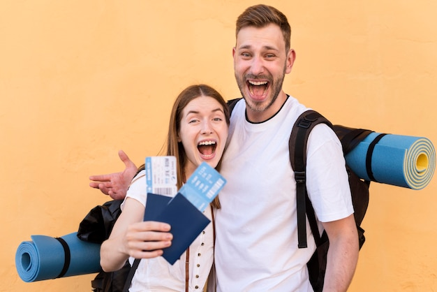 Zijaanzicht van smiley toeristische paar met vliegtickets en paspoorten