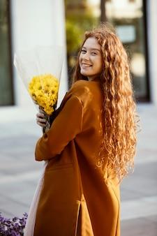 Zijaanzicht van smiley vrouw poseren buitenshuis met lente bloemen boeket
