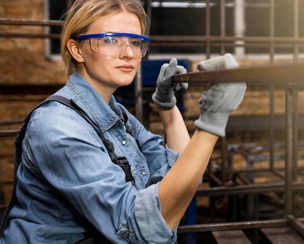 Zijaanzicht van smiley vrouwelijke lasser op het werk