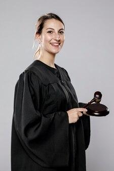 Zijaanzicht van smiley vrouwelijke rechter met hamer
