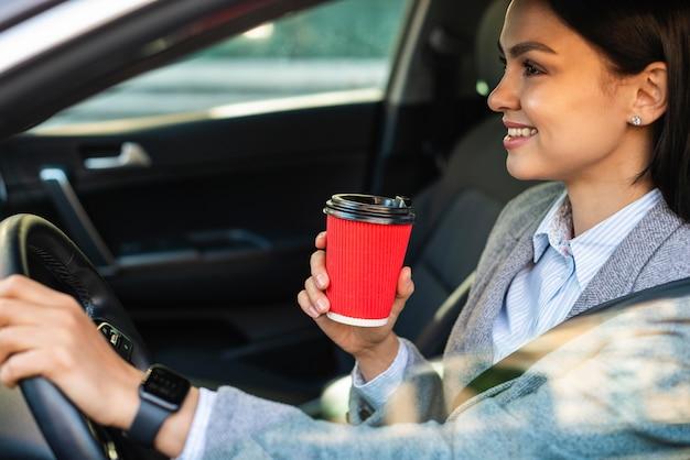 Zijaanzicht van smiley zakenvrouw met haar koffie tijdens het rijden