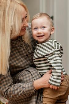 Zijaanzicht van smileygrootmoeder die haar leuke kleinzoon houdt