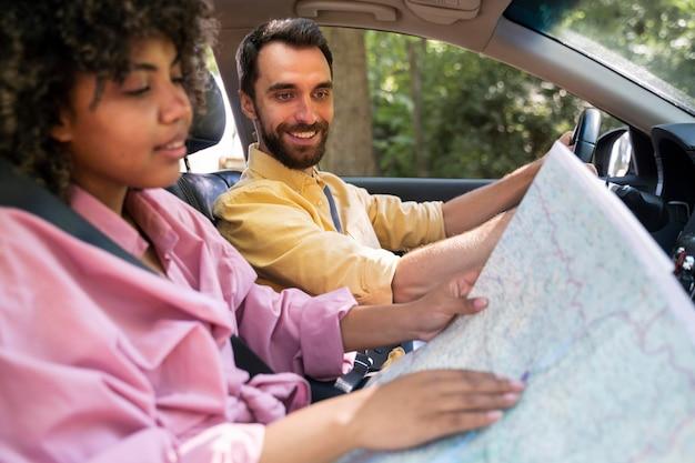 Zijaanzicht van smileypaar in auto raadplegingskaart