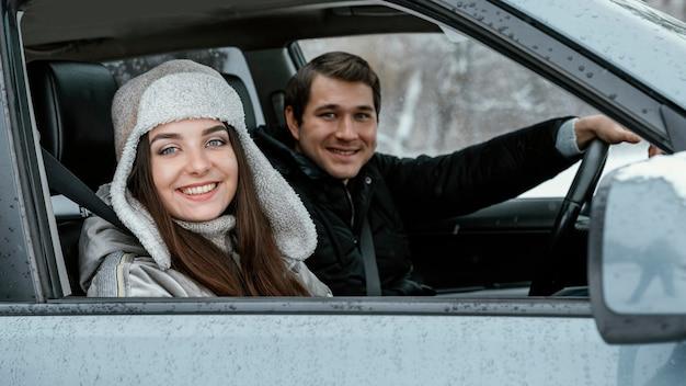 Zijaanzicht van smileypaar in de auto terwijl op een road trip