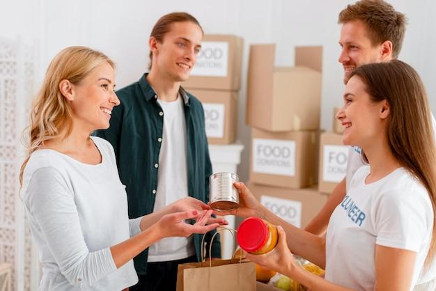 Zijaanzicht van smileyvrijwilligers die voedselschenkingen uitdelen