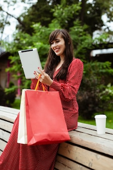 Zijaanzicht van smileyvrouw buiten het bestellen van artikelen te koop met behulp van tablet