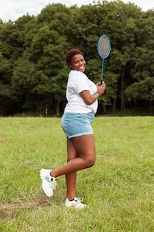 Zijaanzicht van smileyvrouw buitenshuis met racket