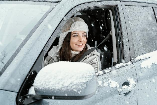 Zijaanzicht van smileyvrouw die de auto drijft voor op een roadtrip