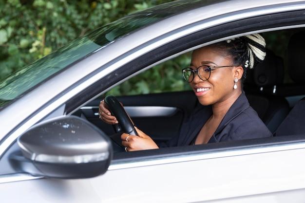 Zijaanzicht van smileyvrouw die haar persoonlijke auto drijft