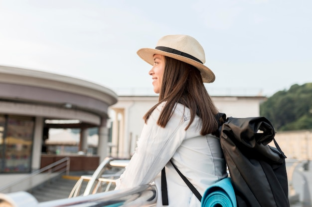 Zijaanzicht van smileyvrouw die het uitzicht bewondert tijdens het reizen